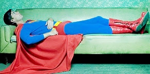Superman laying on couch and thinking