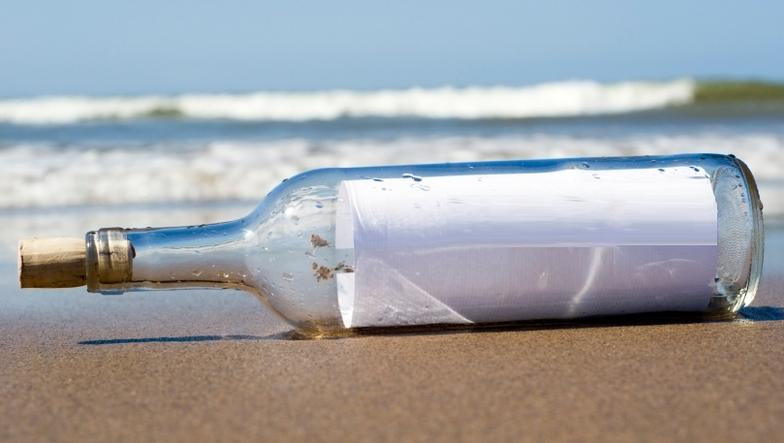 Beach scene; message in bottle containing contact info